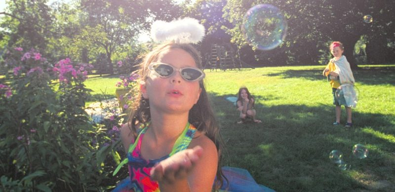 Girl in party dress blowing soap bubbles