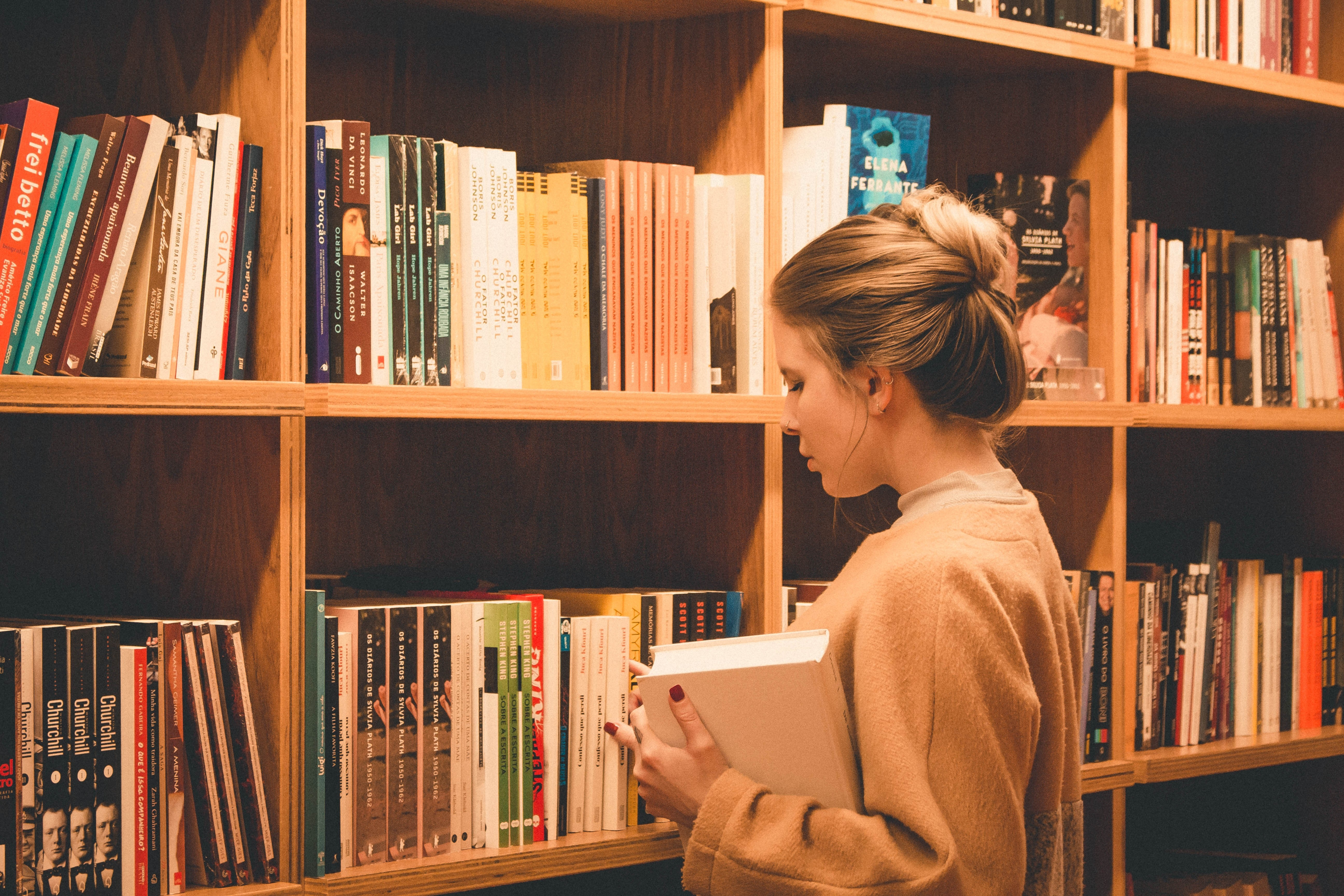 Woman searching the stacks in a library