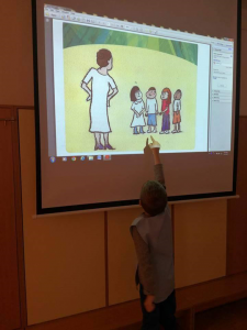 A student pointing at a child in a projected illustration.
